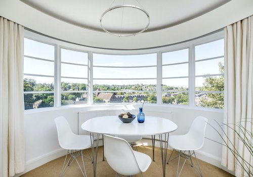 white table and chairs in front of a curved bay window